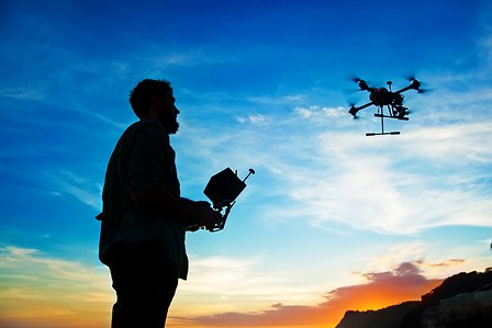 Man playing with a drone against sunset sky