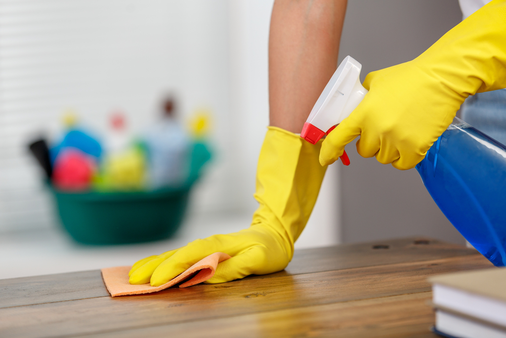 cleaning-table-with-gloves-and-sponge