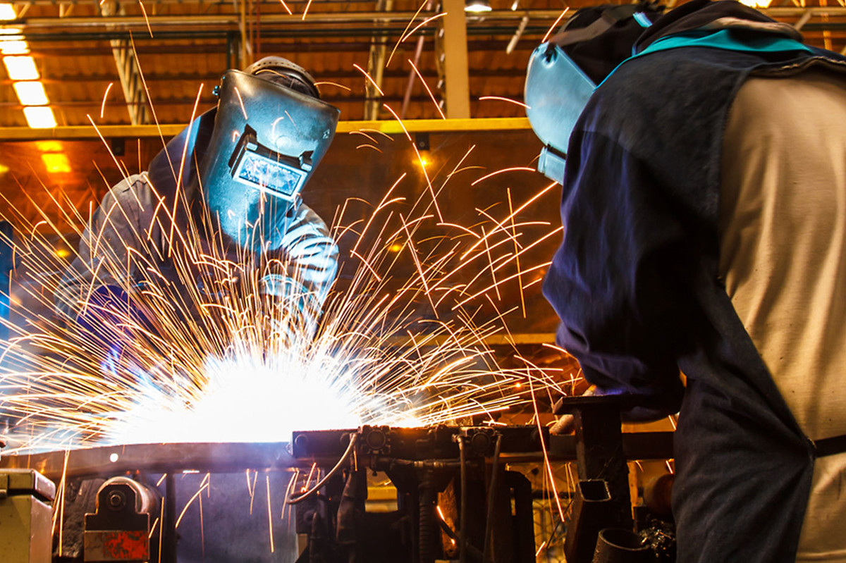 Two men welding with sparks