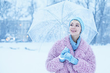 Outdoor portrait of young beautiful happy smiling girl walking in snow-covered street