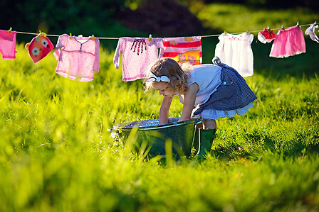 Little girl doing the laundry in the meadow